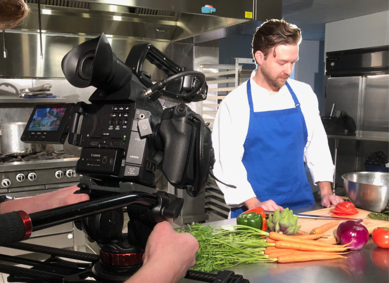 American Bank and Trust video production shoot behind the scenes. Man filming chef cutting vegtables.