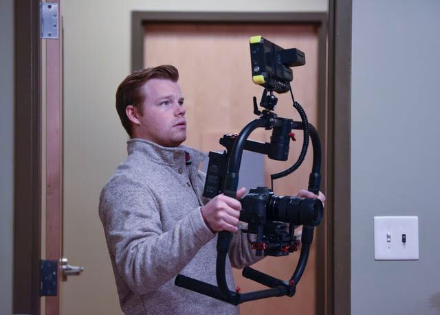 Videographer Nick Johnson filming at Med Center Health in Bowling Green, KY holding a steadicam and camera