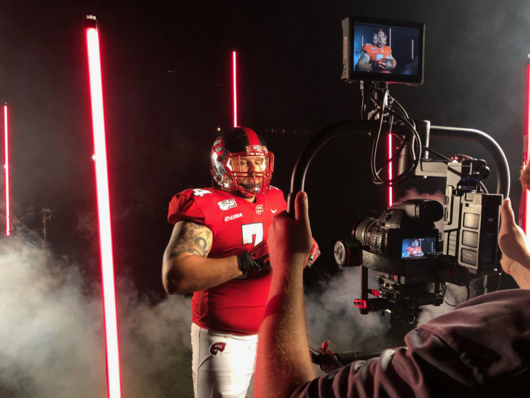WKU Football lineman holds a football and poses in front of red Quasar bulbs and smoke for an intro video shoot with Sublime Media Group