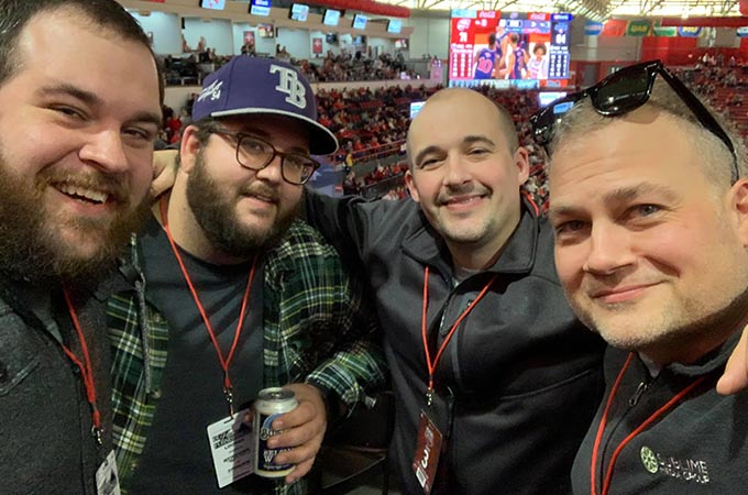 Sublime Media Group's Senior Website Developer Ross Brown, Marketing Strategist Will Kronenberger, Creative Director Austin Albany, and Managing Director Jon Doss posed together at a WKU Basketball home game