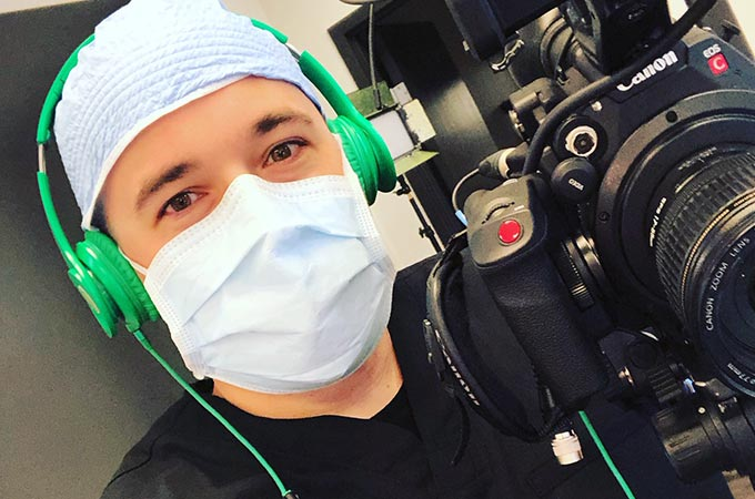Medical Videographer Austin Albany wearing scrubs and a mask while filming a live surgery at Salameh Plastic Surgery center in Bowling Green, KY.