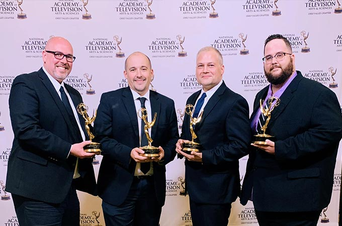 Sublime Media Group Emmy Award Winners David Hosay, Austin Albany, Jon Doss, and Will Kronenberger holding their trophies in front of a step and repeat wall at 2019 Ohio Valley Regional Emmy Awards