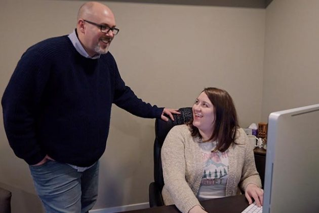 David Hosay and Kayla Bitner Discussing a Social Media Ad Strategy in front of a computer at Sublime Media Group's office in Bowling Green, KY